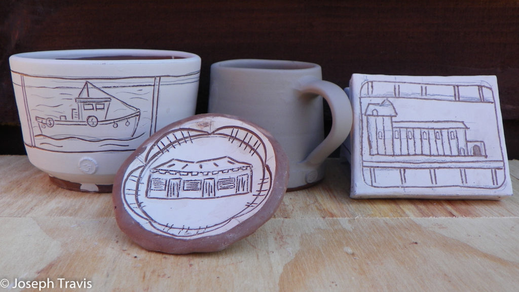 boats and buildings carved on pots that are covered in white clay with red clay showing through the drawings.