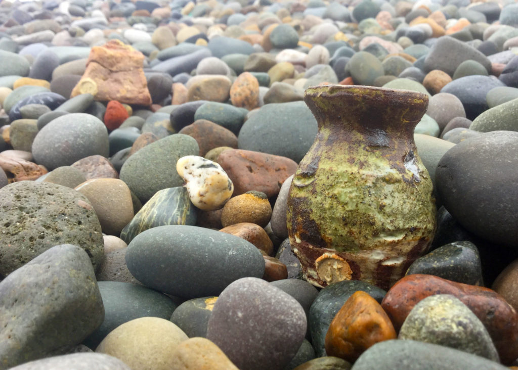 two seaside saggar pots on a pebble beach with similar colours to the pebbles